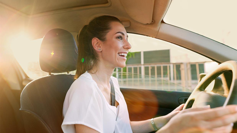 Auto-Abo: junge Frau zufrieden am Steuer eines abonnierten Autos