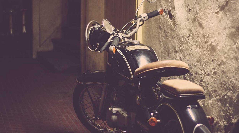 Ein schwarzes Oldtimer-Motorrad vor einer weißen Wand.
