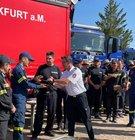 Verbandsführer Michael Brückmann, von der Berufsfeuerwehr Frankfurt, übergibt bei der Verabschiedung von den griechischen Feuerwehrkräften ein Gastgeschenk.
