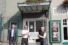 Übergabe des Spendenschecks vor dem Mettmanner Weltspiegel-Kino (von links: Benedikt Lamerz (FFV), Marco Zerweiss (Leiter der Feuerwehr), Thomas Rüttgers (Geschäftsführer ECCOPLEXX Mettmann GmbH)