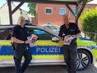 Die Polizeibeamten Alisa Böhm und Christian Rusniok zeigen die Broschüren, die ab Montag in den Briefkästen der Samtgemeinde Boffzen zu finden sind.