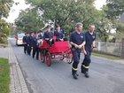 Holger Kopke (links) und Stephan Buche (rechts) bringen Achim Heuer (l) und Reinhard Merchel (r) mit der Bosteler Feuerwehrkutsche zur Jahreshauptversammlung, unterstützt von aktiven Kameradinnen und Kameraden und begleitet vom neuen Mannschaftstransportwagen (Foto: Feuerwehr Bostel)