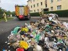 © Feuerwehr Dresden Einsatzkräfte stehen neben dem abgeladenen Inhalt des Müllfahrzeuges.
