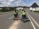 Dien Einsatzkräfte arbeiten im Gefahrenbereich der Hauptverkehrsstraße in Breckerfeld.